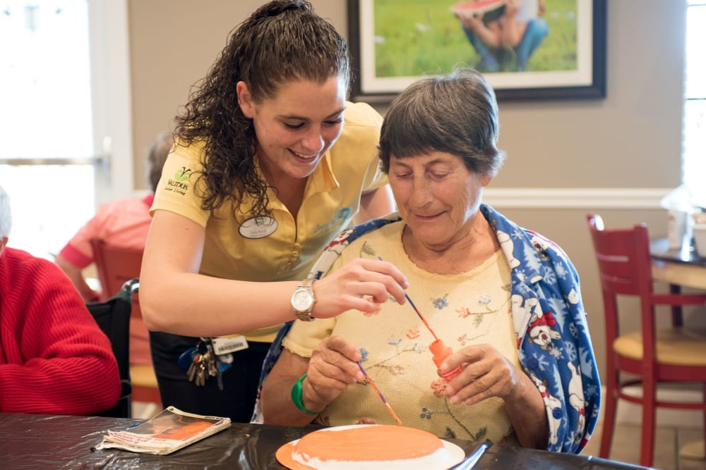 A resident painting with help from a staff member at Inspired Living Alpharetta in Alpharetta, Georgia.