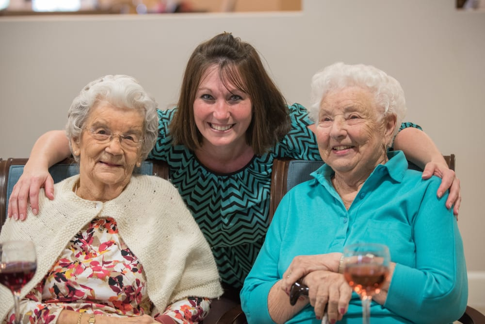 Two residents pose for a picture with a staff member from Inspired Living Alpharetta in Alpharetta, Georgia.