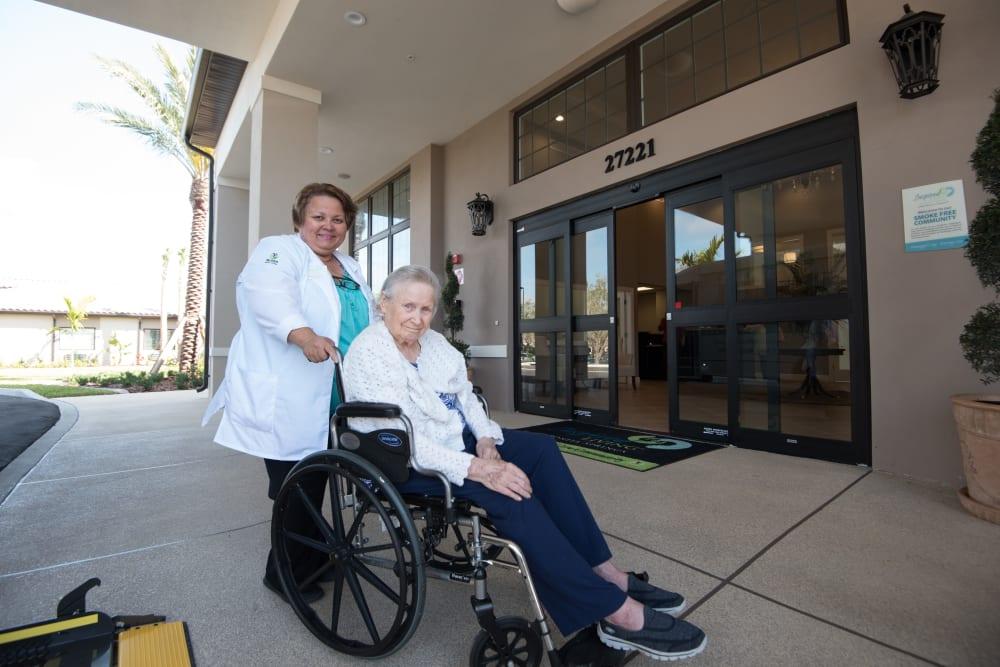A staff member helping a resident in a wheelchair to their room at Inspired Living Alpharetta in Alpharetta, Georgia.