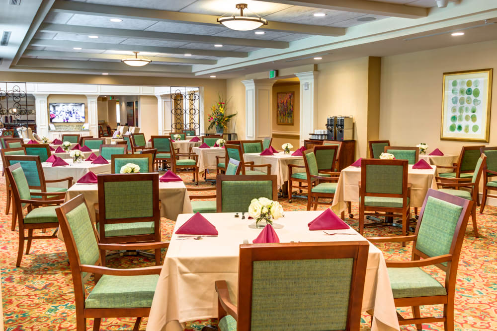 Large dining hall with tables set for four at The Meridian at Boca Raton in Boca Raton, Florida