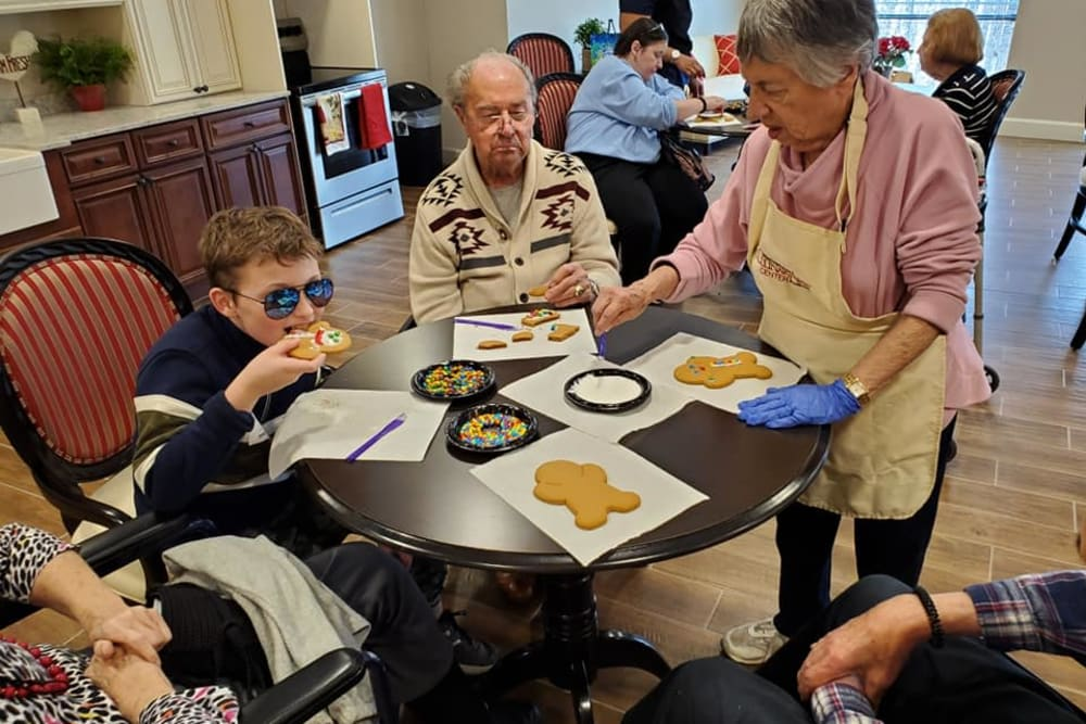 Residents and family members eating cookies at Inspired Living Alpharetta in Alpharetta, Georgia.