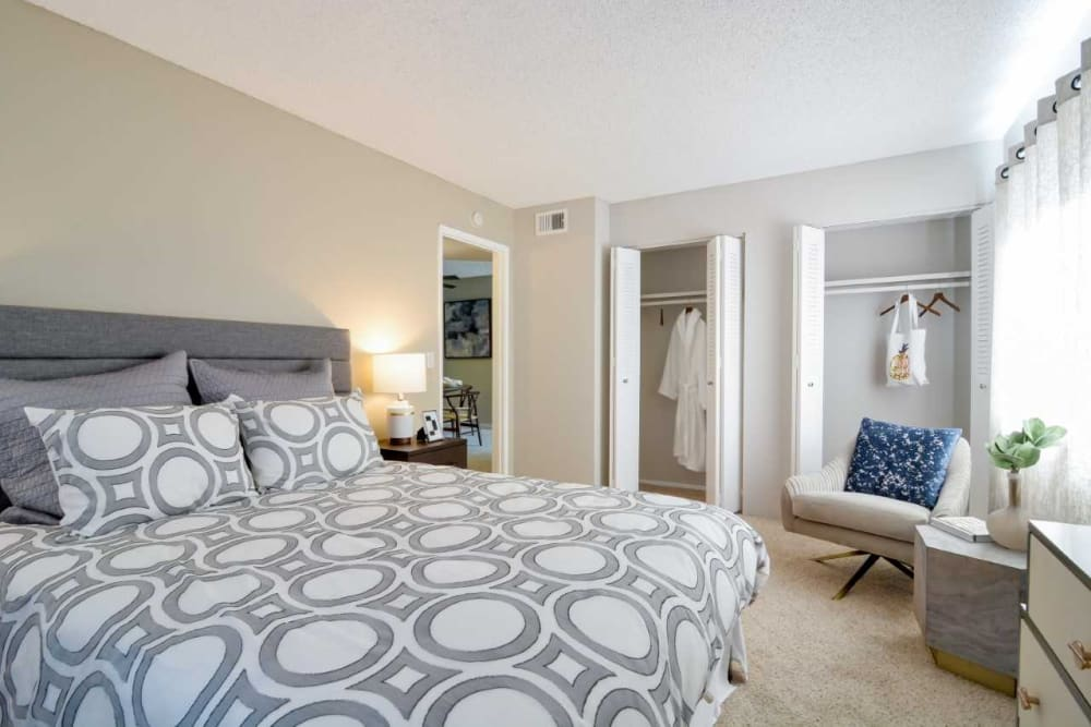 Ample closet space and plush carpeting in a model home's master bedroom at Waterstone Fremont in Fremont, California
