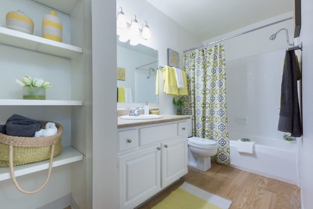 Spacious bathroom with extra shelf space and hardwood flooring in a model home at Waterstone Fremont in Fremont, California