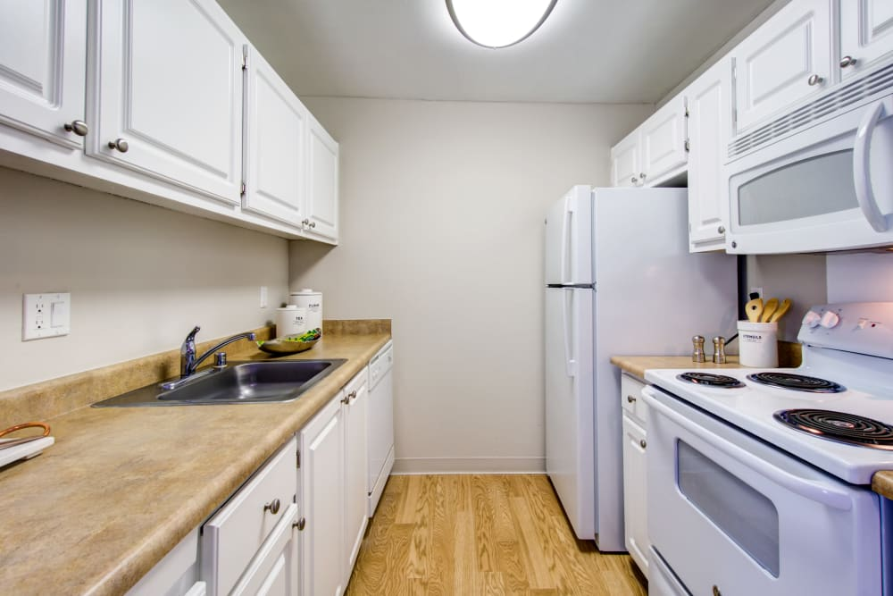 Hardwood flooring and bright white appliances in a model home's kitchen at Waterstone Fremont in Fremont, California