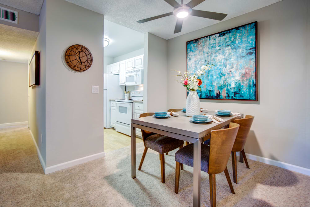 Dining area with a ceiling fan next to the kitchen in a model home at Waterstone Fremont in Fremont, California