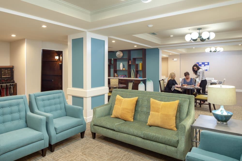 Community common room with a bookshelf and couches at Regency Palms Long Beach in Long Beach, California