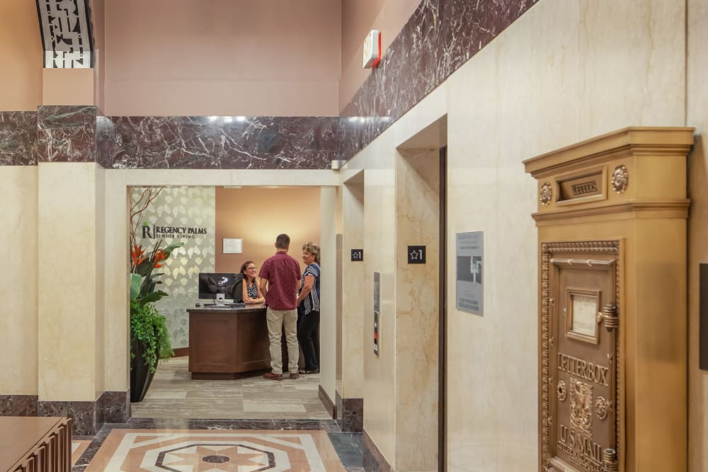 People talking to reception in the lobby at Regency Palms Long Beach in Long Beach, California