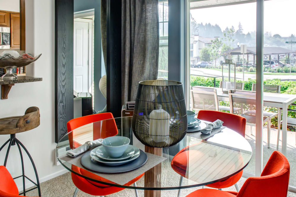 Well-decorated model home's dining area with a view of the private patio outside at Sofi at Cedar Mill in Portland, Oregon