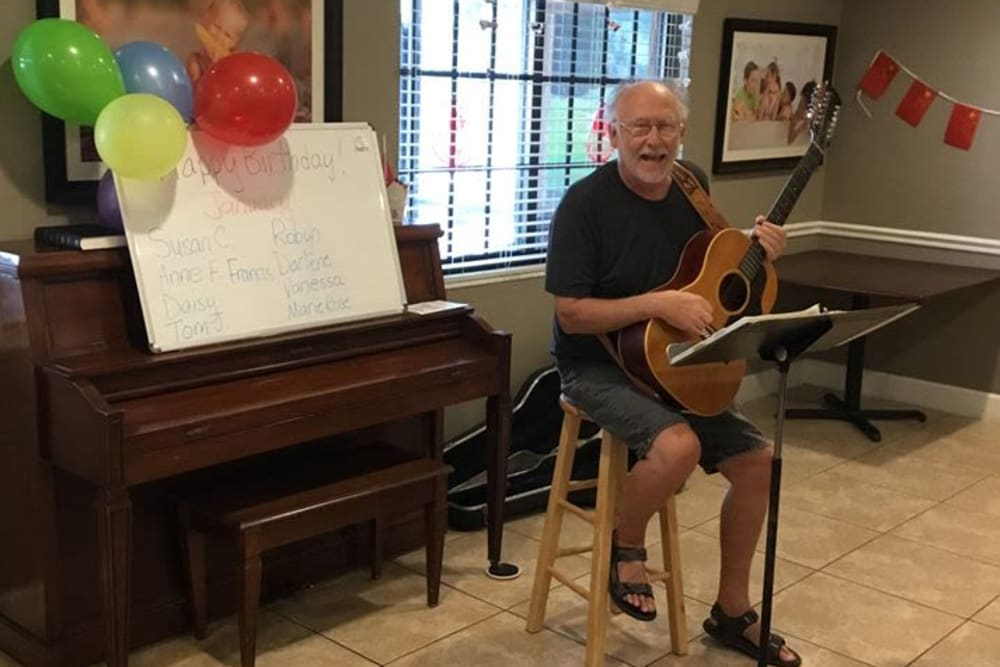 A resident playing the guitar at Inspired Living at Hidden Lakes in Bradenton, Florida.