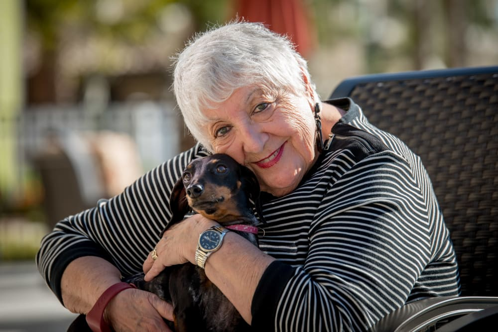 A resident hugging her dog at Inspired Living at Lakewood Ranch in Bradenton, Florida.