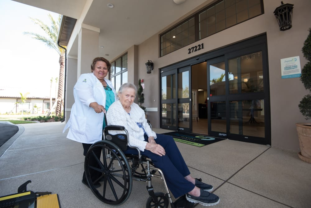 A staff member helping a resident in a wheelchair to their room at Inspired Living at Lakewood Ranch in Bradenton, Florida.