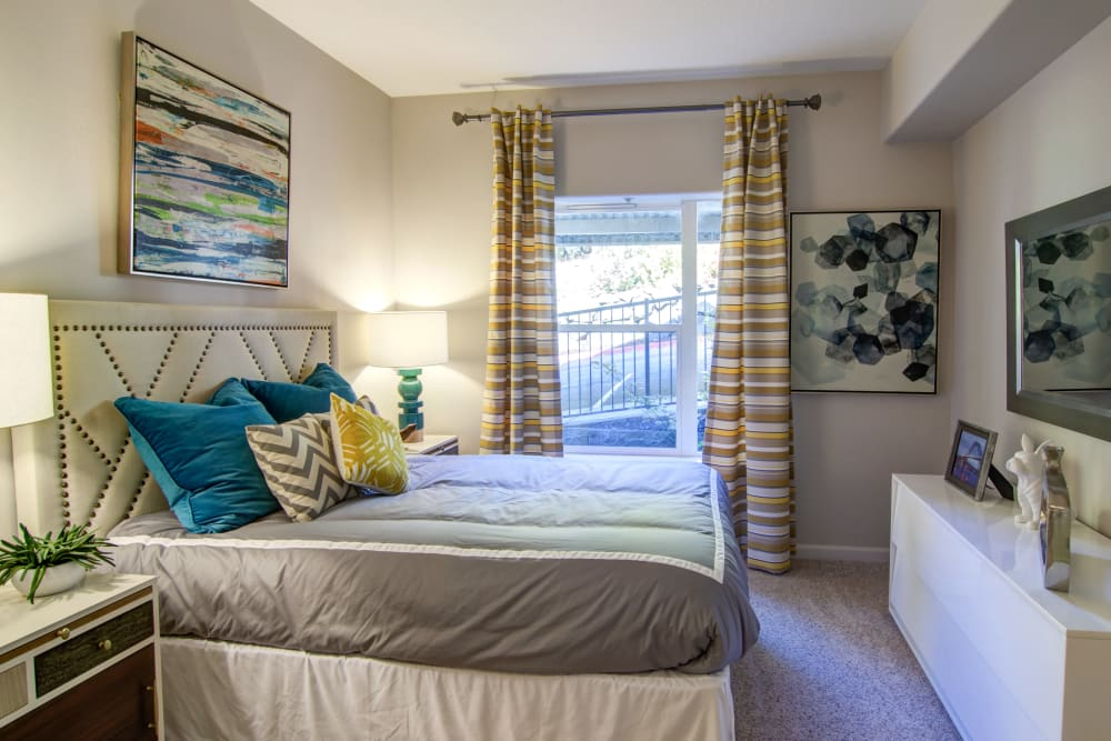 Draped windows and plush carpeting in a model home's bedroom at Sofi at Forest Heights in Portland, Oregon