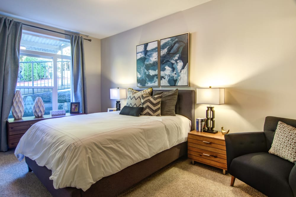 Plush carpeting and modern furnishings in a model home's master bedroom at Sofi at Forest Heights in Portland, Oregon