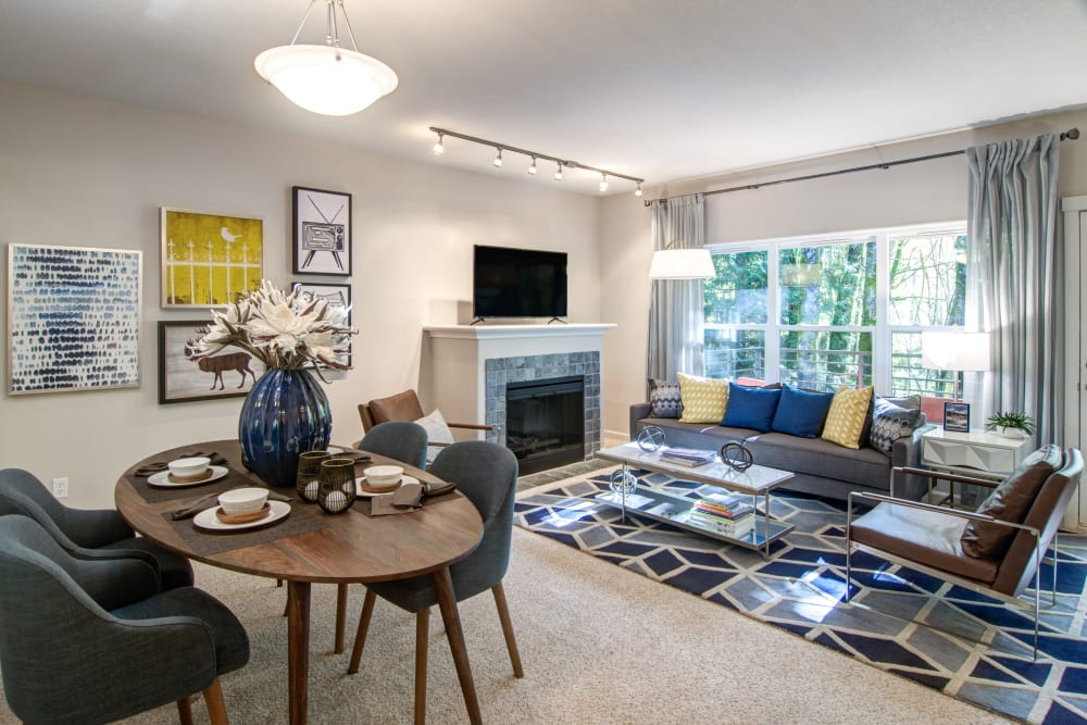 Spacious open-concept living area with a fireplace in a model home at Sofi at Forest Heights in Portland, Oregon