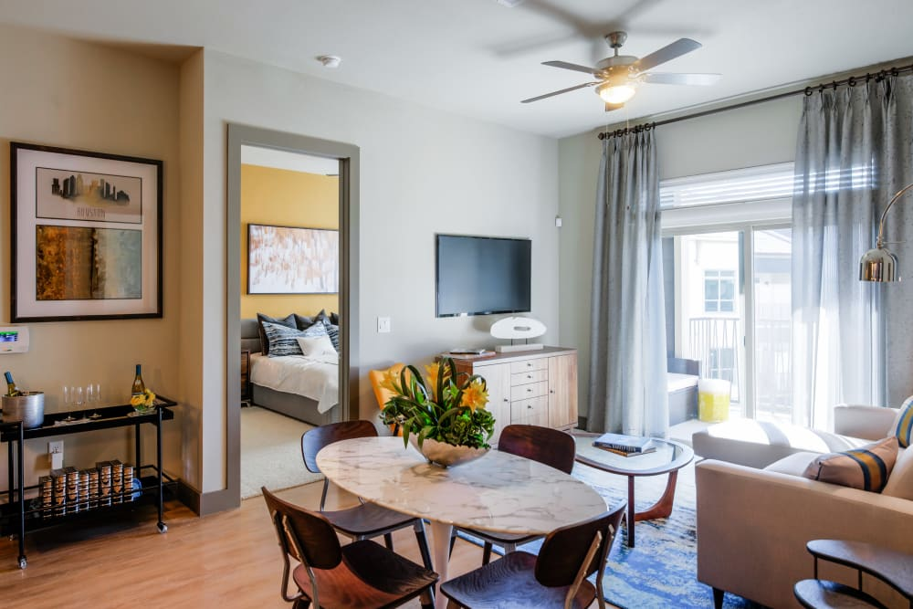 An apartment living room and bedroom at The Abbey at Northpoint in Spring, Texas