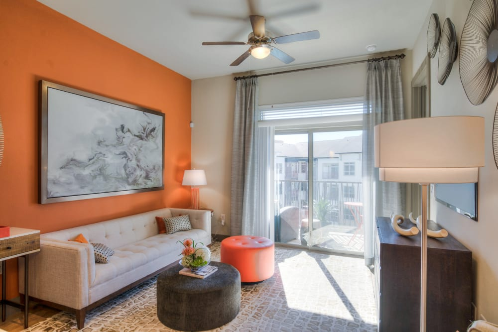 A living room with an orange wall at The Abbey at Northpoint in Spring, Texas