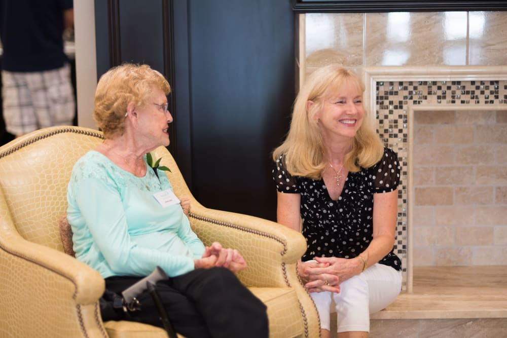 A resident chatting with a staff member at Inspired Living Royal Palm Beach in Royal Palm Beach, Florida.