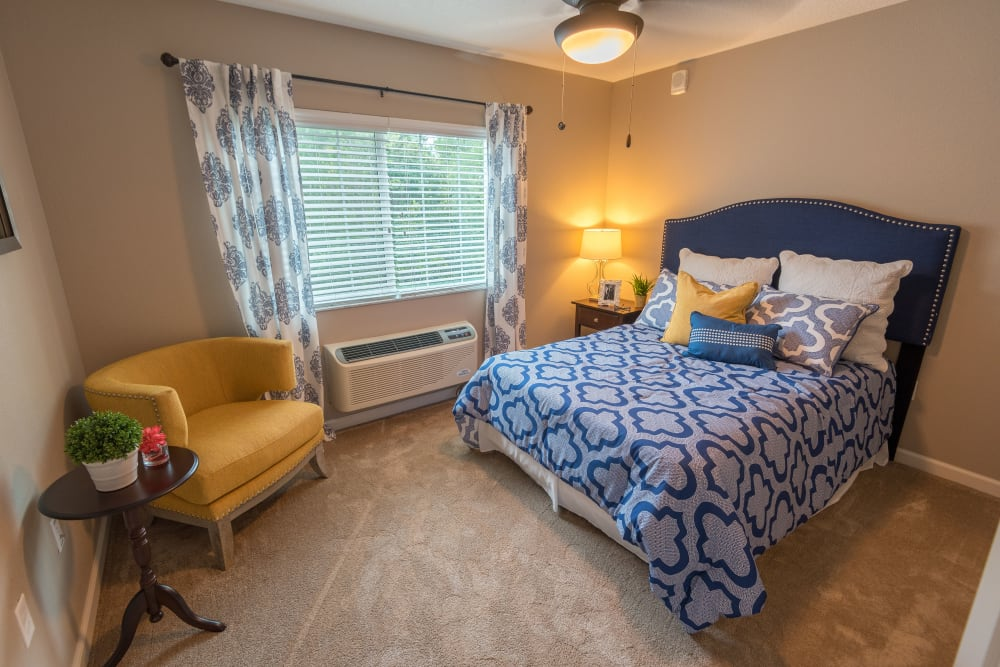 Model resident bedroom with a large window at Inspired Living at Royal Palm Beach in Royal Palm Beach, Florida.