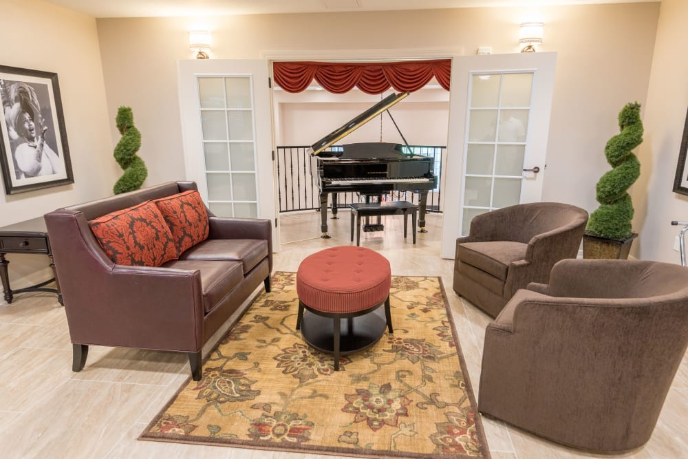 Lounge area with a piano at Inspired Living in Royal Palm Beach, Florida.