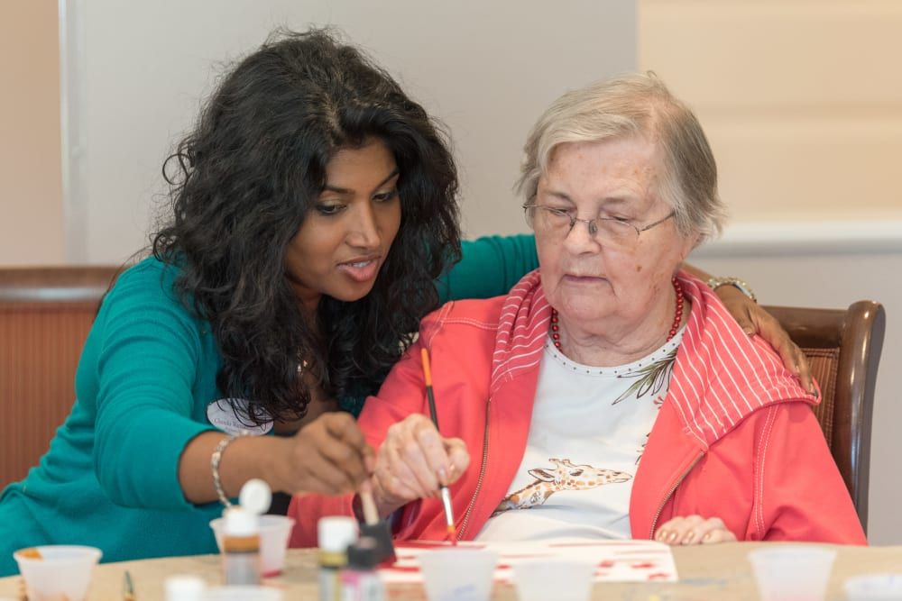A staff member helping a resident with an art project at Inspired Living Royal Palm Beach in Royal Palm Beach, Florida.