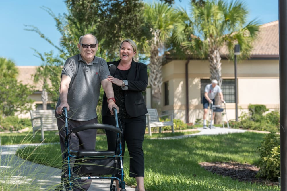 Resident out for a walk with a staff member at Inspired Living Royal Palm Beach in Royal Palm Beach, Florida.