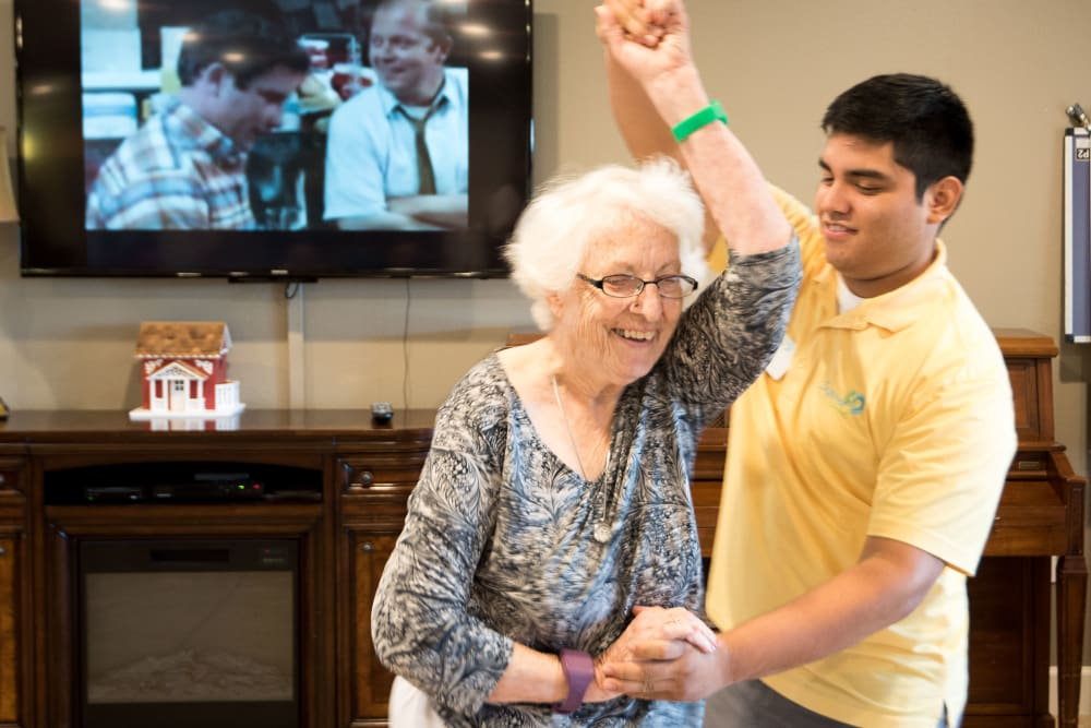 Staff member dancing with a resident at Inspired Living at Sugar Land in Sugar Land, Texas.