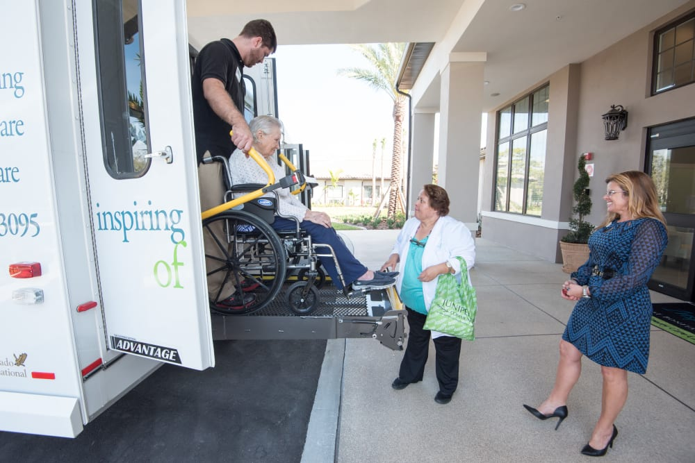 Staff helping a resident off a bus at Inspired Living at Sugar Land in Sugar Land, Texas.