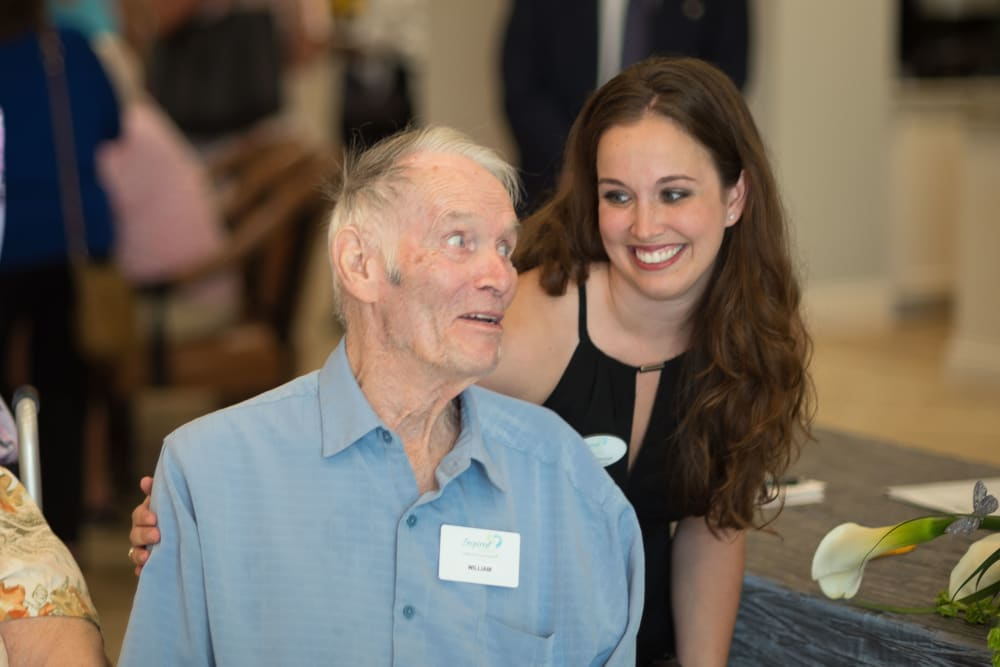 Staff member saying hello to a resident at an event at Inspired Living at Sugar Land in Sugar Land, Texas.