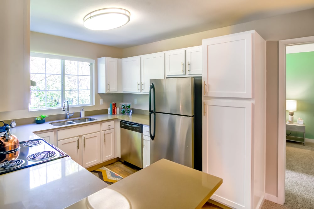 Stainless-steel appliances and bright white cabinetry in a model home's kitchen at Sofi at Murrayhill in Beaverton, Oregon