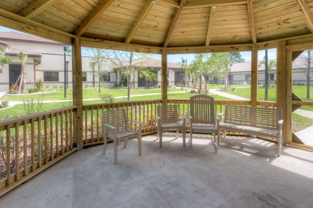 Shaded gazebo with chairs and benches at Inspired Living Tampa in Tampa, Florida.