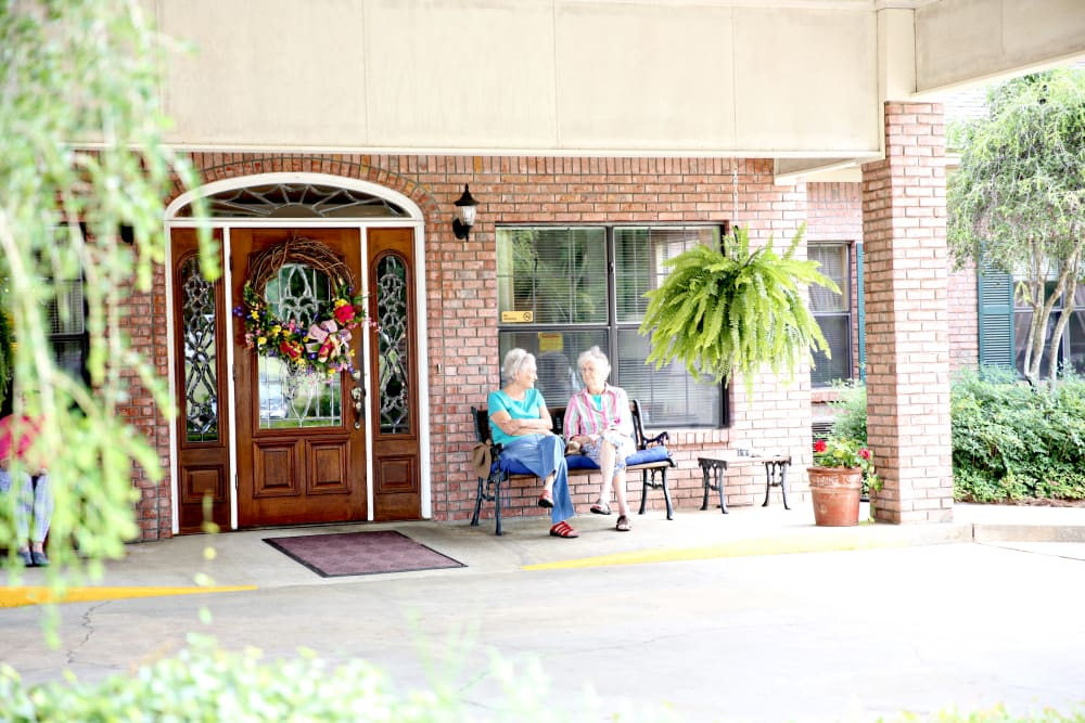 Two resident friends sitting outside at Providence Assisted Living in Grenada, Mississippi.