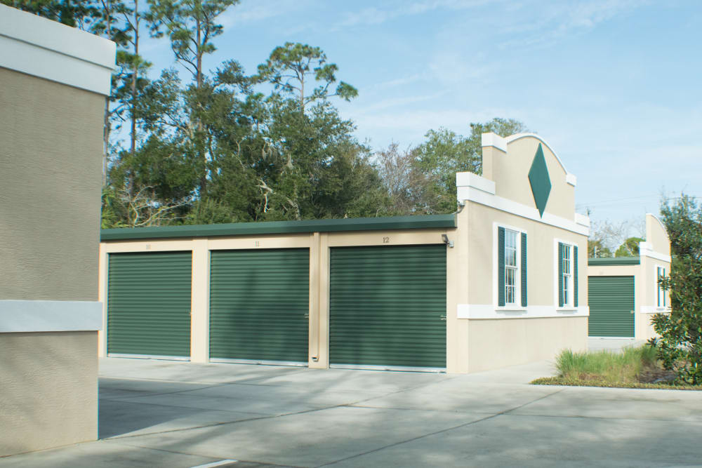 Outdoor storage units surrounded by trees at Best American Storage in Ormond Beach, Florida