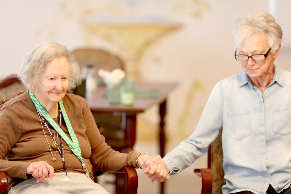 Two resident friends holding hands at Providence Assisted Living in Springdale, Arkansas