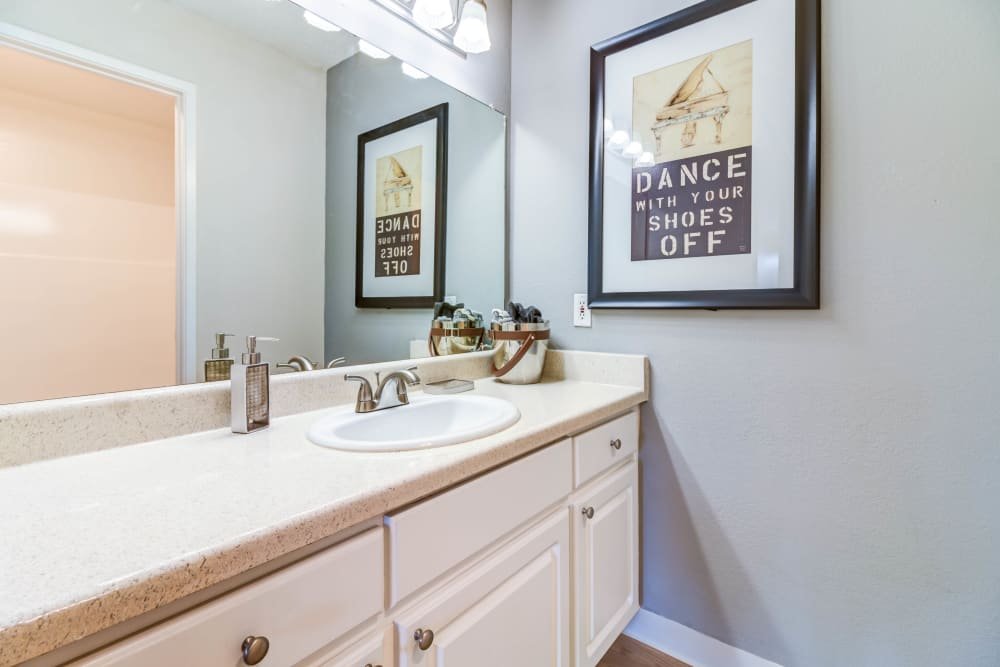 Well-lit bathroom with a large vanity mirror and ample counter space in a model home at The Landmark Apartment Homes in Sunnyvale, California