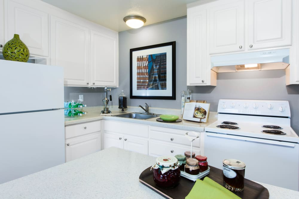 Quartz countertops and white cabinetry in a model home's kitchen at The Landmark Apartment Homes in Sunnyvale, California