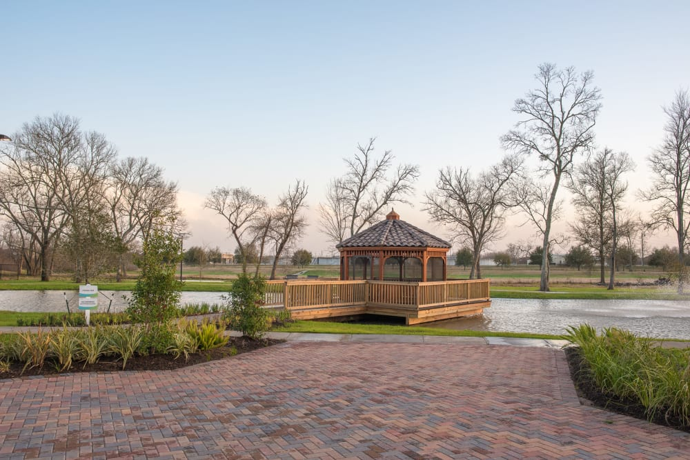 Gazebo on a pond surrounded by bushes at Inspired Living Sugar Land in Sugar Land, Texas.