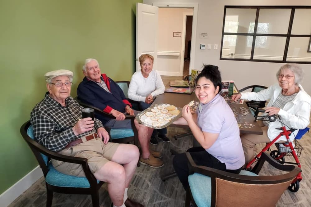 Residents enjoying cookies while putting together a puzzle at Atrium at Liberty Park in Cape Coral, Florida