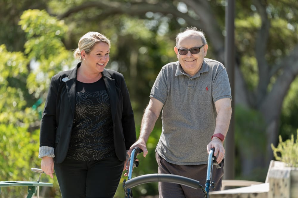 Staff member walking with a resident at Inspired Living Tampa in Tampa, Florida