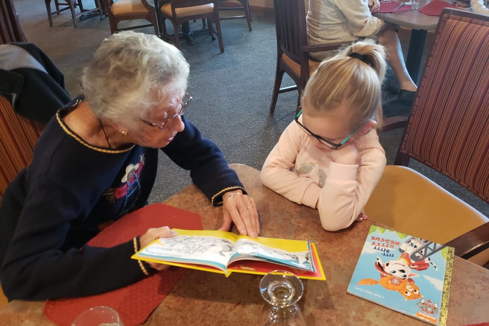 A resident and a child reading a book at Landings of Oregon in Oregon, Ohio