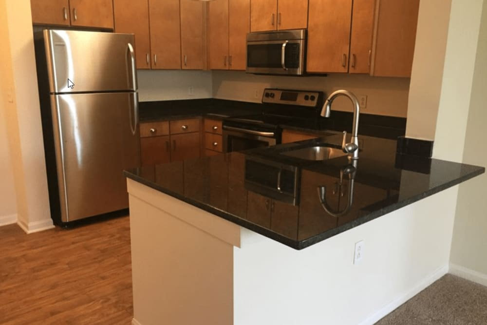 Modern kitchen appliances, cabinetry and hardwood flooring at Westville Village Apartments in New Haven, Connecticut