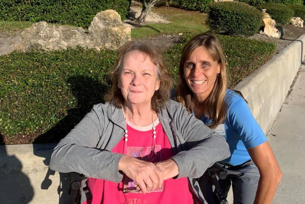 A resident and a staff member enjoying some sunshine outside at Lake Morton Plaza in Lakeland, Florida
