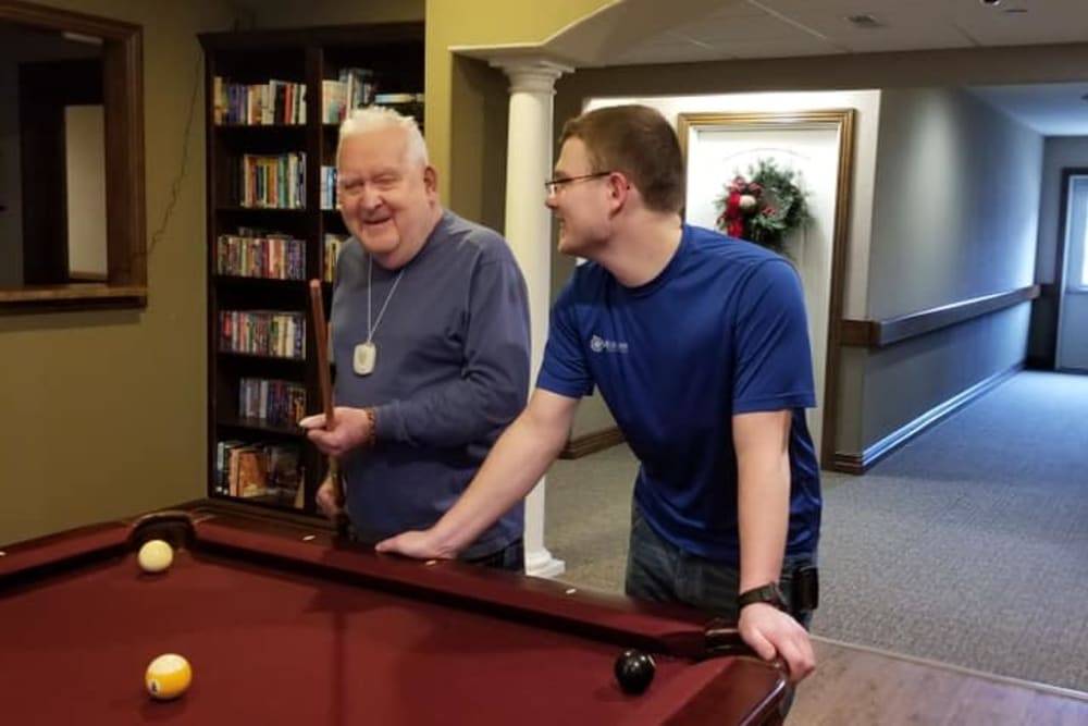 A resident and staff member playing pool at Villas of Holly Brook Shelbyville in Shelbyville, Illinois