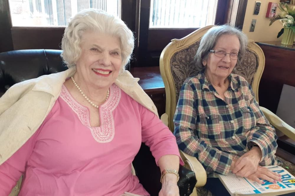 Two residents smiling for the camera at Cedar Crest Memory Care in Lafayette, Louisiana