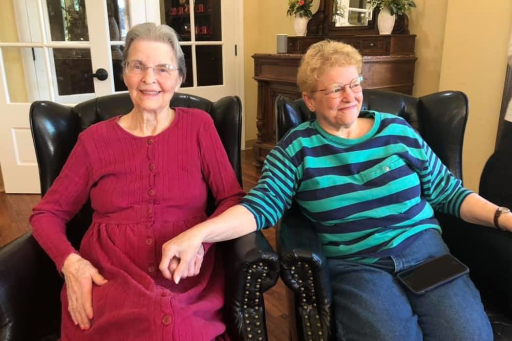 Two residents holding hands at Cedar Crest Memory Care in Lafayette, Louisiana