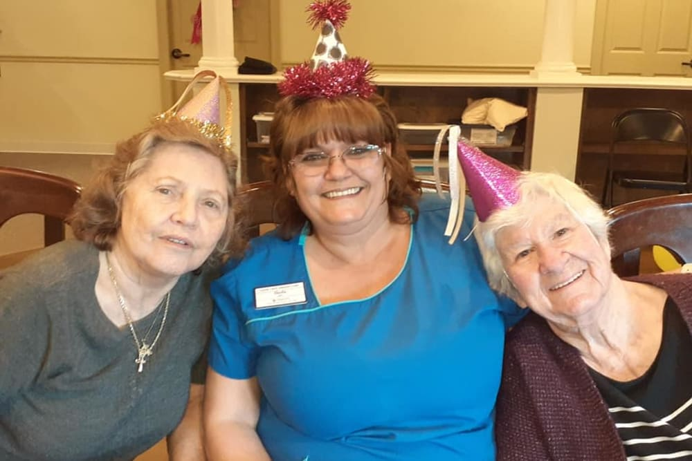 Residents and a caregiver celebrating at Cedar Crest Memory Care in Lafayette, Louisiana