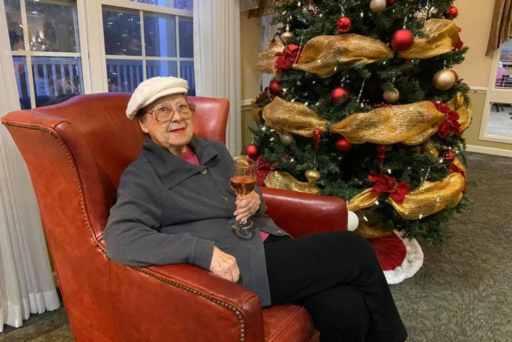 A resident sitting in front of a Christmas tree at The Crossings at Bon Air in Richmond, Virginia