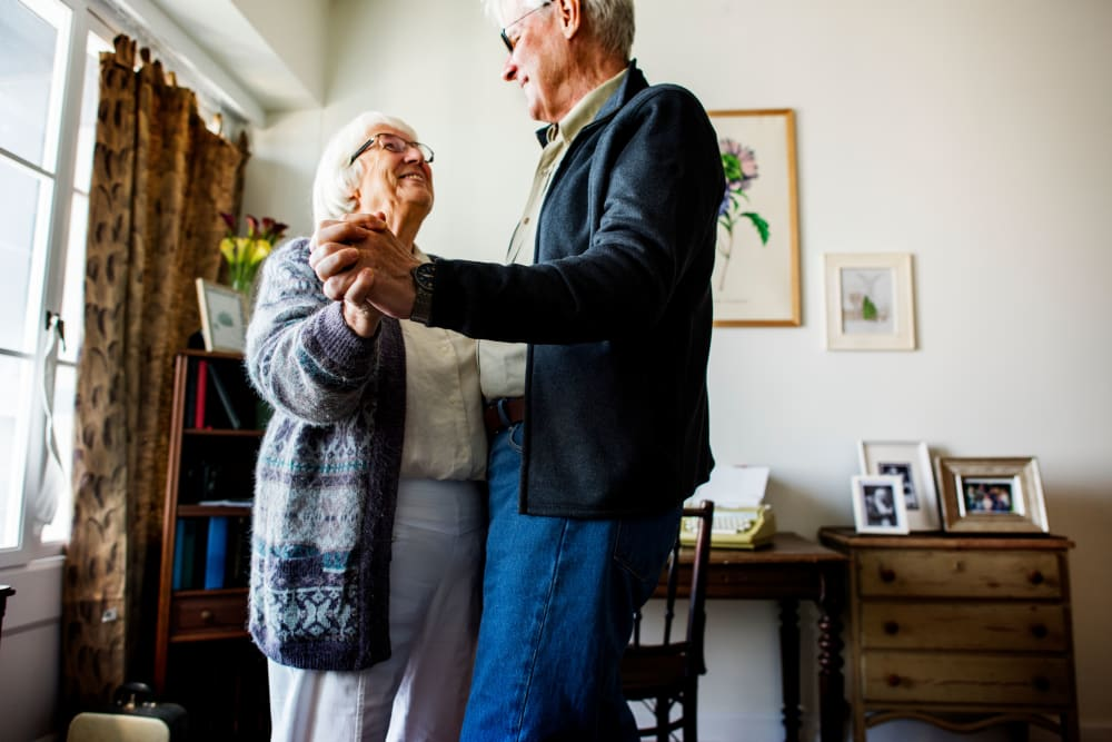Two seniors dancing in their new apartment at a Randall Residence community