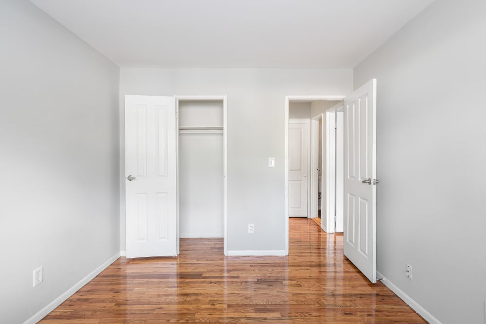Bedroom with polished hardwood floors at Mid Island Apartments in Bay Shore, New York