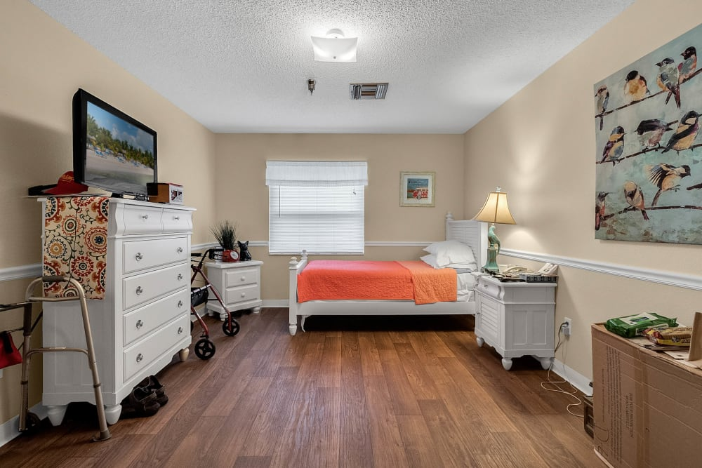 Model bedroom with twin bed and dresser at Forest Oaks of Spring Hill