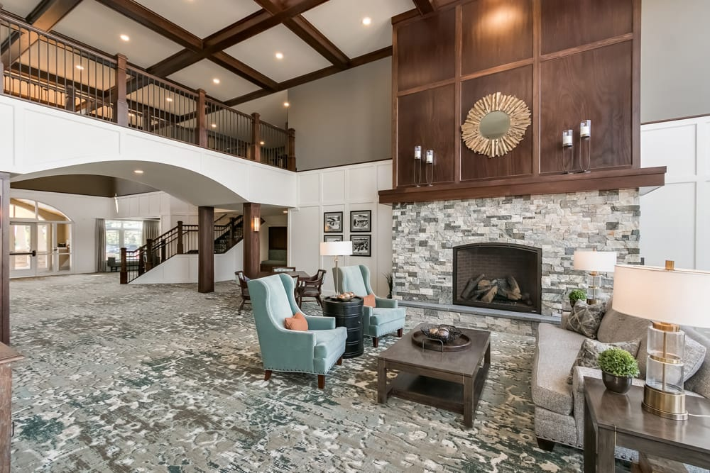 Seating area next to a fireplace at Applewood Pointe of Champlin at Mississippi Crossings in Champlin, Minnesota.